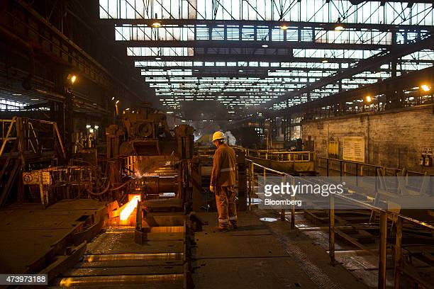 A worker watches as a red hot steel billet moves along an automated conveyor system at the Celsa Steel UK Ltd steel mill in Cardiff UK on Monday May...