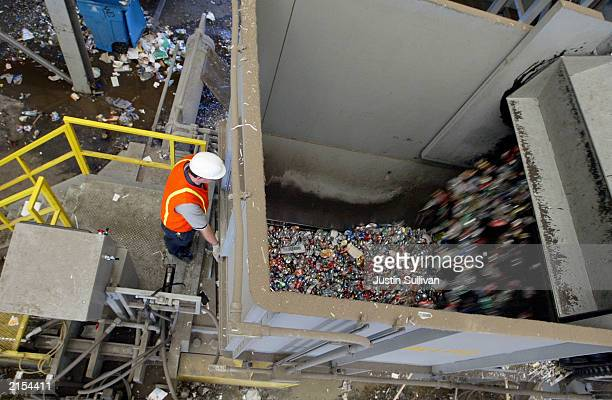A worker watches as aluminum cans are emptied into a bailer at the Norcal Waste recycling facility July 11 2003 in San Francisco The most modern...