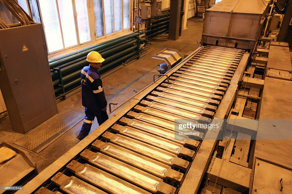 A worker watches as aluminum ingots cool as they pass along the production line in the foundry at the Irkutsk aluminium smelting plant, operated by United Co. Rusal, in Shelekhov, Russia, on Monday, Sept. 21, 2015. The biggest aluminum producers are discussing the introduction of a 'green' trademark for the lightweight metal that could be sold at a premium and encourage carbon footprint reductions among rivals, United Co. Rusal's deputy chief executive officer said. Photographer: Andrey Rudakov/Bloomberg via Getty Images