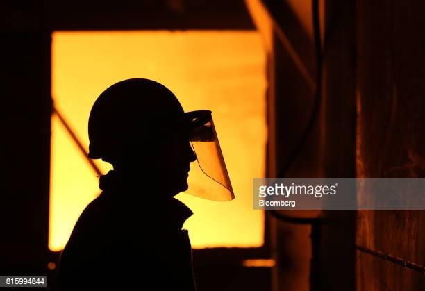 A worker watches as an electric arc furnace operates in the smelting shop at the Oskol Elektrometallurgical Plant steel mill operated by...
