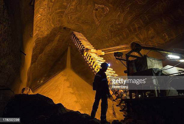A worker watches as excavated potash pours from the tunnel ceiling into an underground storage area at a potash mine operated by OAO Uralkali in...
