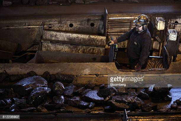 A worker watches as large lumps of coking coal move along a conveyor belt in a processing facility above ground in the Piniowek coal mine operated by...