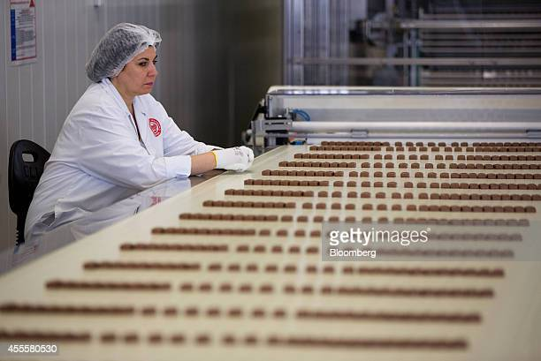 A worker watches as Nesquik nougat confectionary passes along a conveyor belt during production at the Rossiya chocolate factory operated by Nestle...