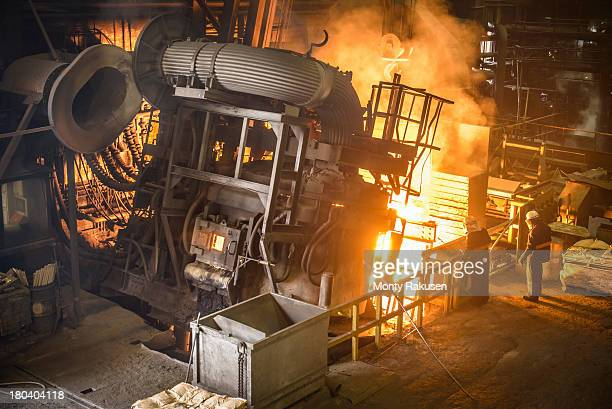 Worker watching large electric furnace pouring steel in industrial foundry
