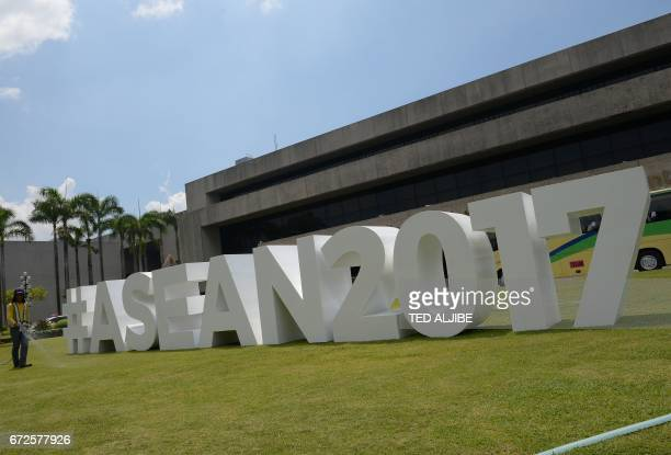 A worker waters the grounds around an ASEAN logo outside the Philippine International Convention Center venue for the Association of Southeast Asian...