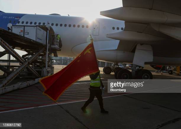 Worker waves China's national flag as one million doses of the Sinopharm Group Co Ltd.Vaccine are delievered at Nikola Tesla Airport in Belgrade,...
