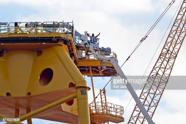 A worker waves from the top of one of the giant steel structures for offshore wind power developments which dominate the Methil yard of engineering...
