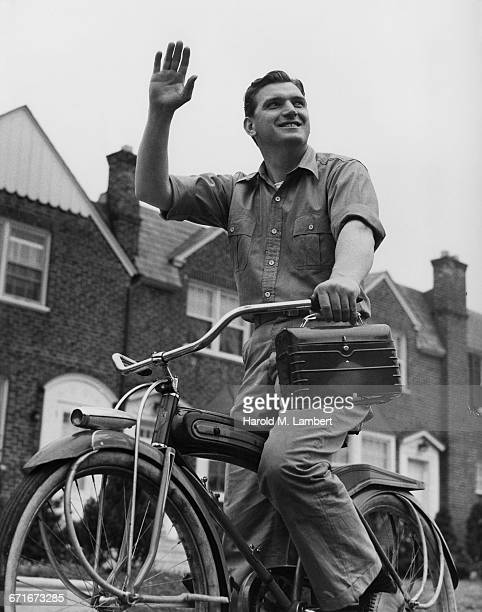 worker waving his hand and holding toolbox while riding on bicycle - {{ contactusnotification.cta }} stockfoto's en -beelden