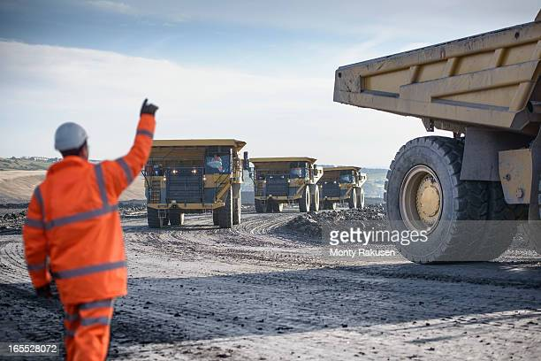 worker waving on dumpers driving on track at surface coal mine - coal mine stock pictures, royalty-free photos & images