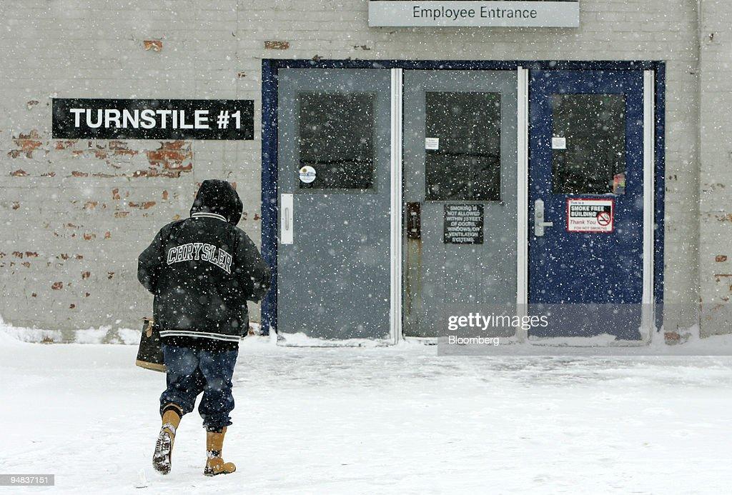 A worker wearing a Chrysler jacket walks toward the Detroit