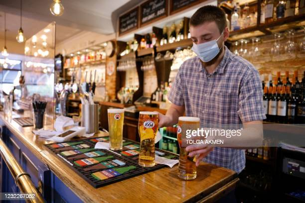 Worker wearing a face covering prepares pints of lager for a customer's drinks order to be taken their outside table at a re-opened pub in east...