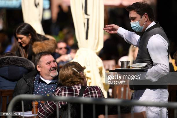 Worker wearing a face covering takes customers' orders as they sit at an outside table at a re-opened pub in Liverpool, north west England, as...