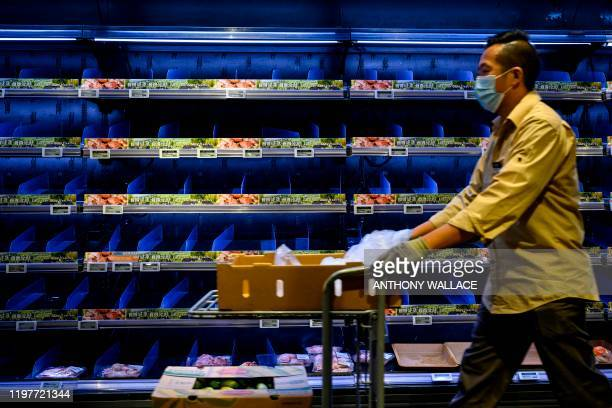 A worker wearing a face mask and gloves as a preventative measure following a virus outbreak which began in the Chinese city of Wuhan pushes a...