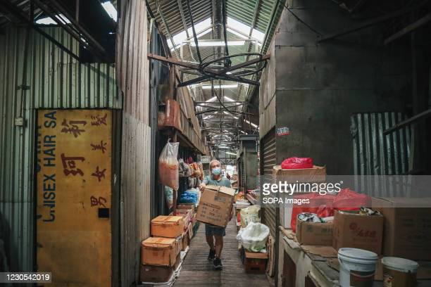 Worker wearing a face mask as a preventative measure against the spread of coronavirus carries a box of goods at the market in Kuala Lumpur. As...
