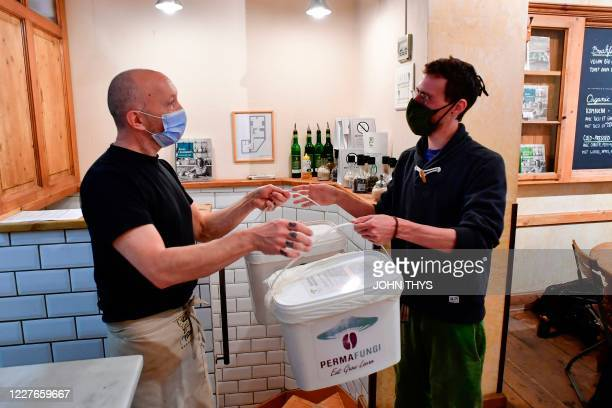 A worker wearing a face mask gives a container to a man to collect coffee grounds from a shop in Brussels on July 15 for the company Permafungi which...