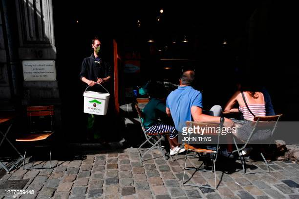 A worker wearing a face mask holds a container after collecting coffee grounds from a shop in Brussels on July 15 for the company Permafungi which...