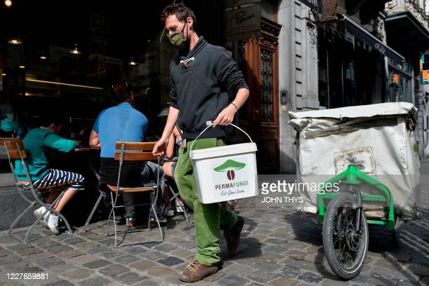 A worker wearing a face mask holds a container as he prepares to collect coffee grounds from a shop in Brussels on July 15 for the company Permafungi...