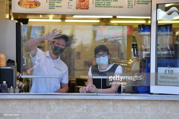 Worker wearing a face mask in a fish and chip shop waves at the photographer from behind a screen on the seafront on June 09, 2021 in Southend on...