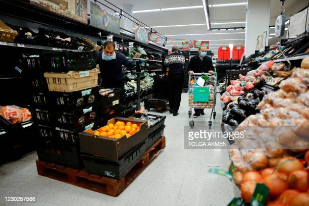 Worker wearing a face mask or covering due to the COVID-19 pandemic, prepares to re-stock fruit and vegetable shelves inside an ASDA supermarket in...
