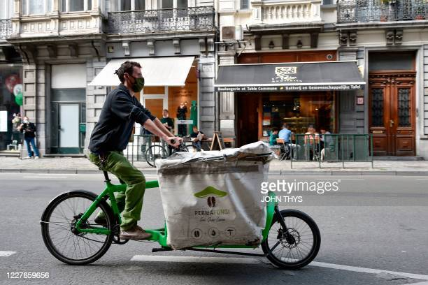 A worker wearing a face mask rides a bike as he prepares to collect coffee grounds from a shop in Brussels on July 15 for the company Permafungi...
