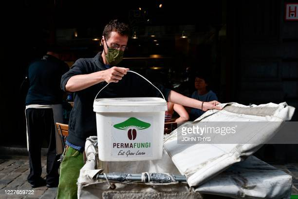 A worker wearing a face mask wearing a face mask holds a container as he prepares to collect coffee grounds from a shop in Brussels on July 15 for...
