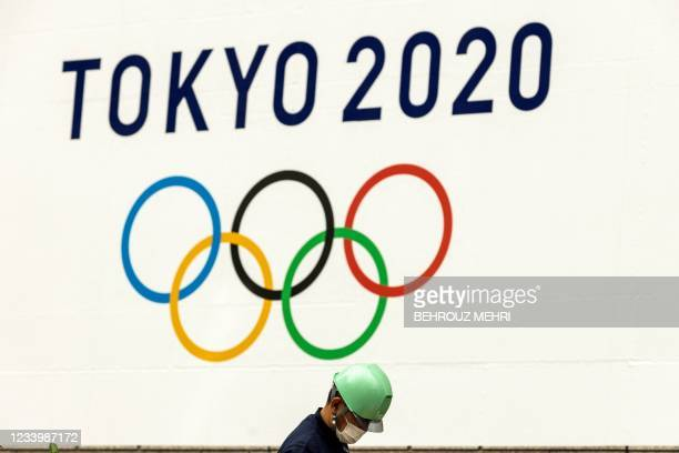 Worker wearing a face mask works under a logo of the Tokyo 2020 Olympic Games in Tokyo on July 15, 2021.