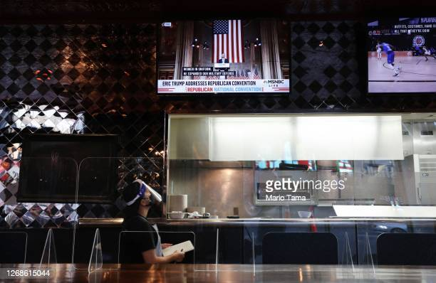 Worker wearing a face shield watches as Eric Trump speaking in a live broadcast of the Republican National Convention is televised on screen in a...