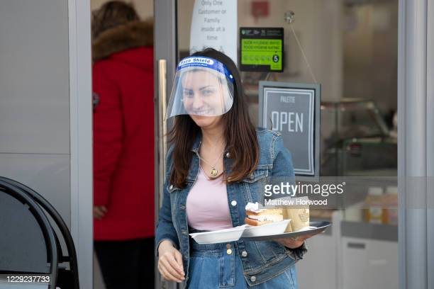 A worker wearing a face visor carries food and drink on a tray to a customer at a coffee shop on St Mary Street on October 23 2020 in Cardiff Wales...