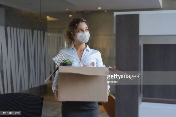 worker wearing a facemask at the office while holding a box with her belongings after being fired - quitting a job stock pictures, royalty-free photos & images