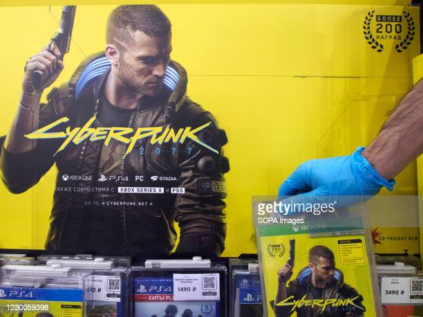 Worker wearing a glove displays a game disc on the shelf. Cyberpunk 2077 is a 2020 action role-playing video game on sale worldwide. In Russia it has...