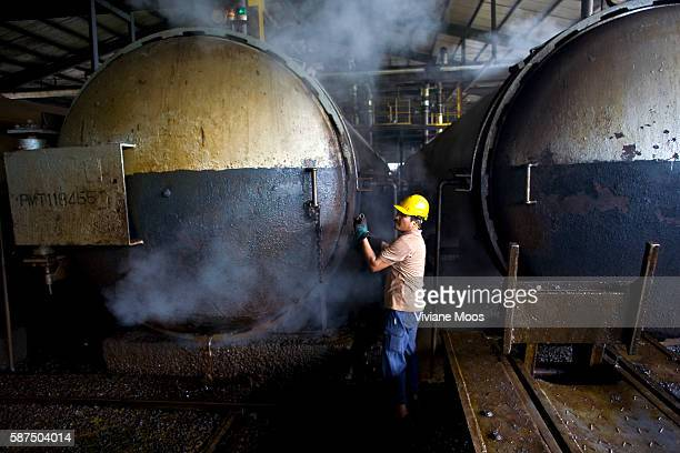 A worker wearing a hard hat and gloves carefully releases the steam from giant pressure cooker vats that sterilize the palm oil fruit before...