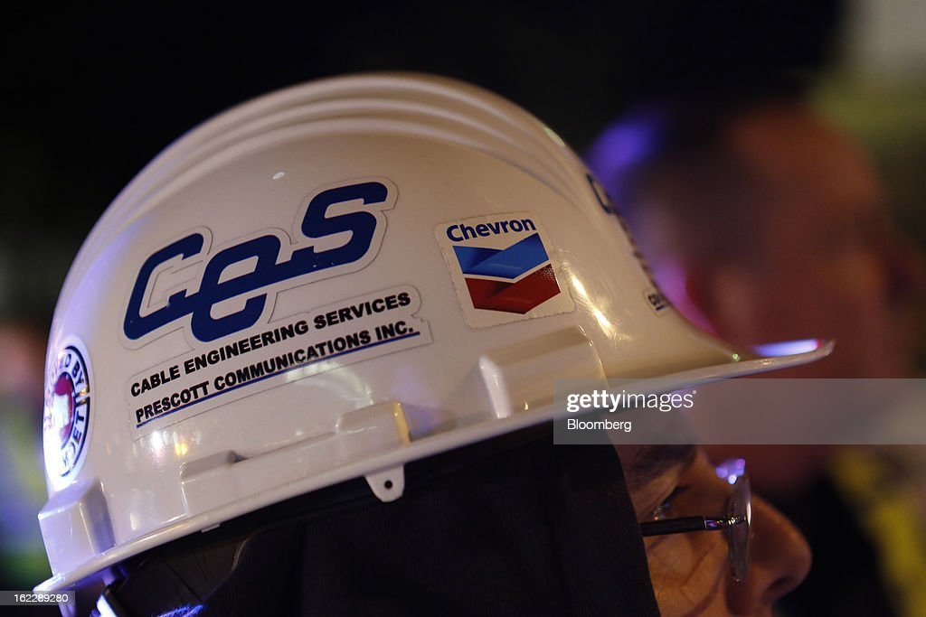 A worker wearing a hard hat monitors the transport of steel coke drums in Redondo Beach, California, U.S., on Wednesday, Feb. 20, 2013. The drums, which measure over 100 feet long and weigh more than 500,000 pounds each, are being transported from Redondo Beach to Chevron's refinery in El Segundo. Photographer: Patrick T. Fallon/Bloomberg via Getty Images