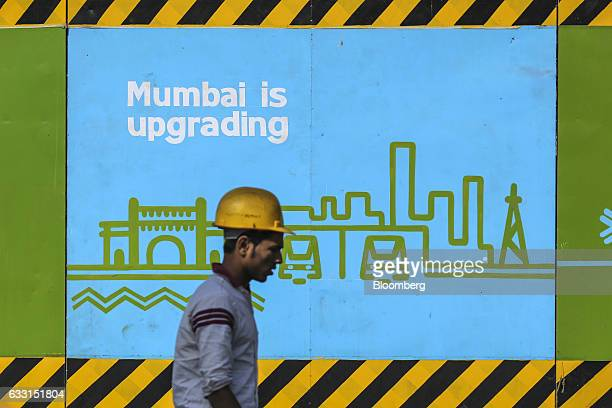 A worker wearing a hard hat walks past a billboard displayed on a construction barricade in Mumbai India on Friday Jan 27 2017 India's Finance...