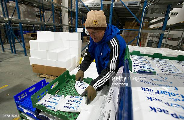 A worker wearing a hat and gloves packs frozen PolarPack gel packs into each order before boxes are sealed and shipped at a United Parcel Service Inc...