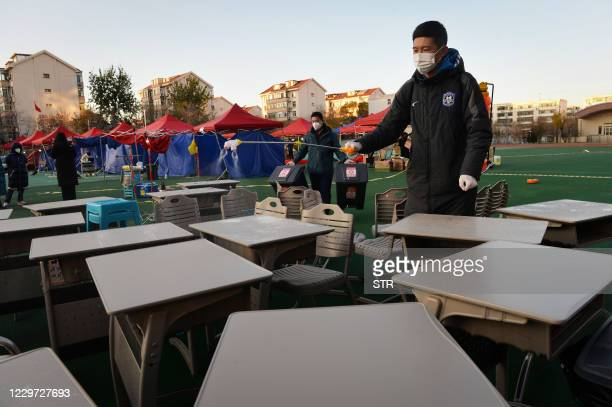 Worker wearing a mask sprays disinfectant on desks at a makeshift testing centre in Tianjin on November 22 after new coronavirus cases were detected...