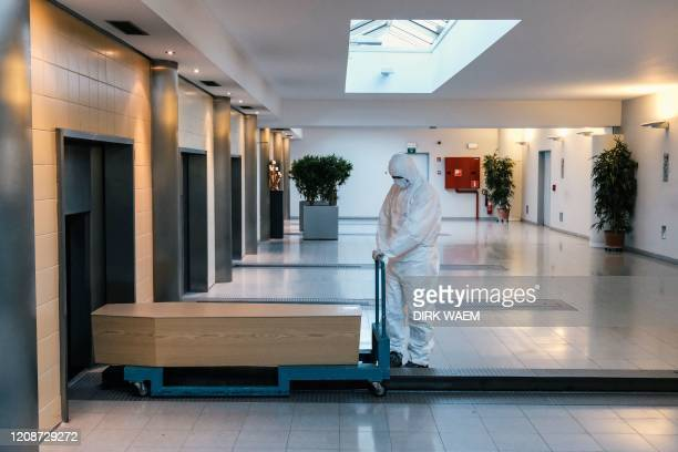 Worker, wearing a personal protective equipment , carries a coffin in the cremation of coronavirus victim at the Wilrijk crematory in Antwerp, on...