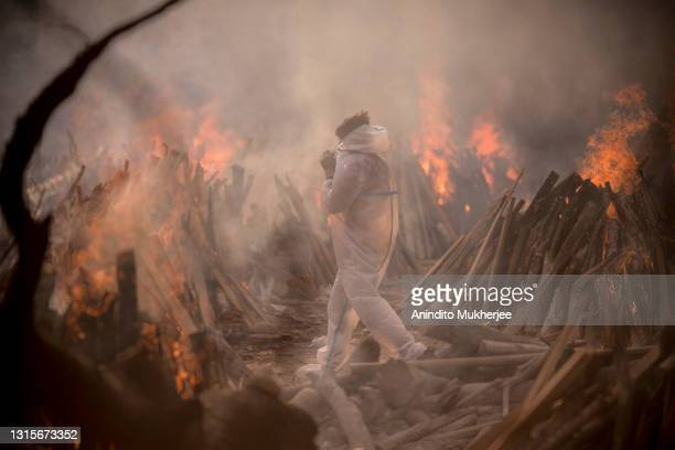 Worker wearing a PPE suit is seen amid the burning funeral pyres of patients who died of COVID-19 at a crematorium on May 01, 2021 in New Delhi,...