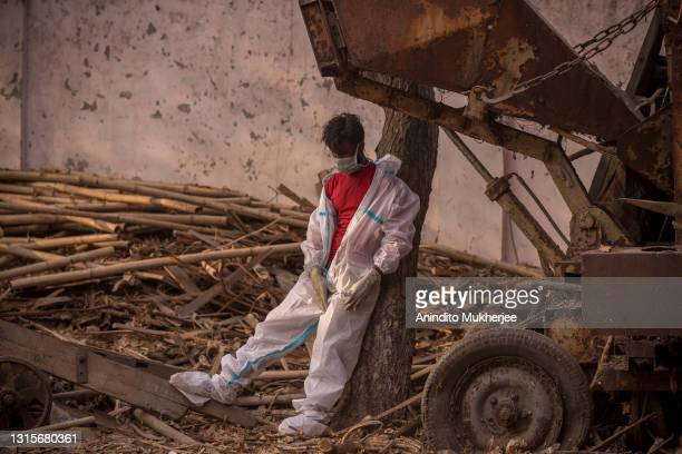 Worker wearing a PPE suit takes a momentary break as people perform the last rites of patients who died of COVID-19 during a mass cremation held at a...
