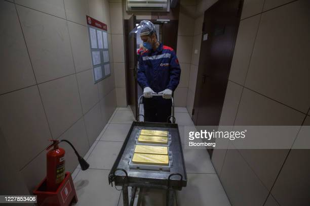 Worker wearing a protective face mask and facial visor moves a trolley containing 12.5 kilogram gold ingots at the Uralelectromed Copper Refinery,...