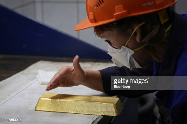 Worker wearing a protective face mask inspects a 12.5 kilogram gold ingot at the Uralelectromed Copper Refinery, operated by Ural Mining and...