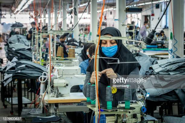 Worker wearing a protective face mask prepares cotton spools on a sewing machine for the manufacture Iranian of brand jeans, including Koi designed...