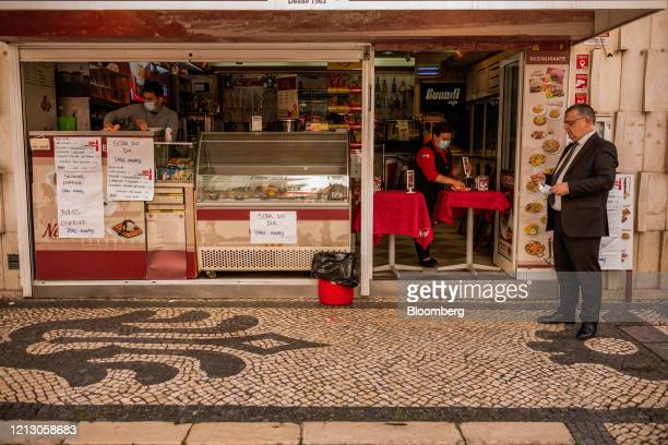 Worker wearing a protective face mask serves takeaway orders at a cafe at Rua Agosta, Lisbon, Portugal on Thursday, May 14, 2020. The European Unions...