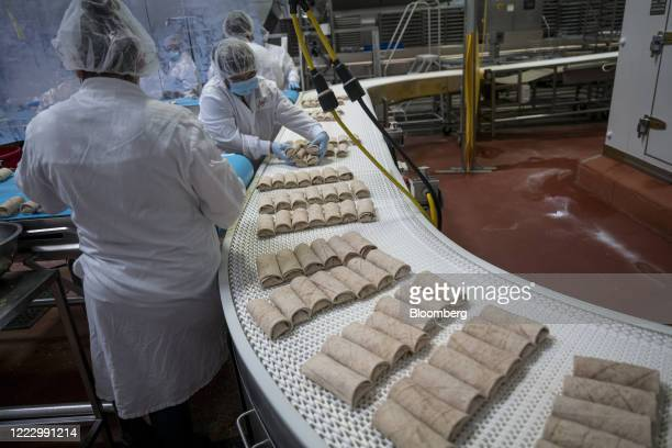 Worker wearing a protective mask and food processing clothing places burritos onto a conveyor belt at an Amy's Kitchen facility in Santa Rosa...