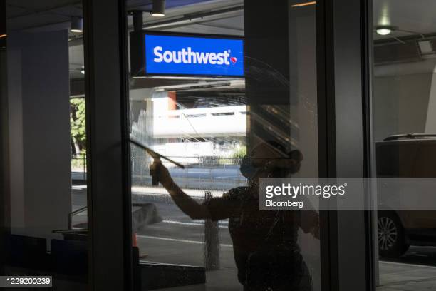Worker wearing a protective mask cleans a window outside a Southwest Airlines Co. Check-in area at San Francisco International Airport in San...