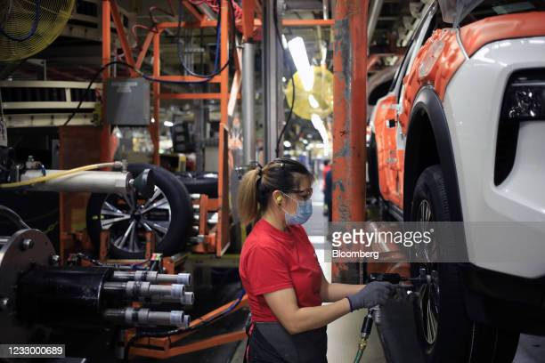 Worker wearing a protective mask installs wheels on a vehicle on the assembly line at the Nissan Motor Co. Manufacturing facility in Smyrna,...