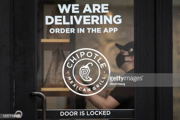 A worker wearing a protective mask puts a food order on a shelf inside a Chipotle Mexican Grill Inc restaurant in San Francisco California US on...