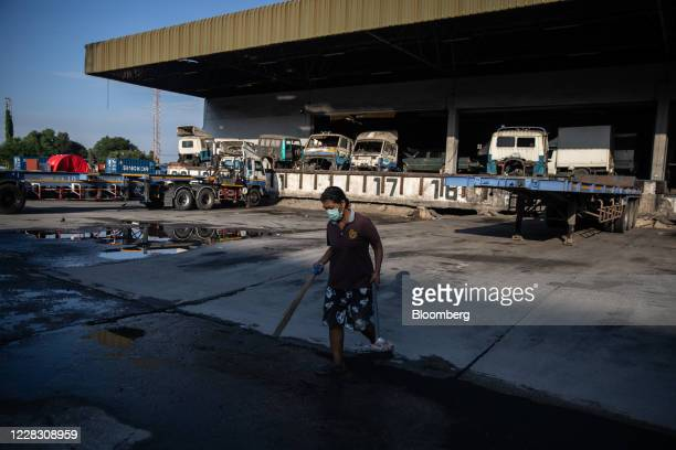 A worker wearing a protective mask sweeps near a logistics building near the port in Bangkok Thailand on Wednesday Sept 2 2020 Thailand has reported...