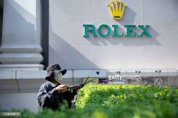 A worker wearing a protective mask trims plants outside a Rolex Group store in Bangkok Thailand on Wednesday Sept 2 2020 Thailand has reported zero...