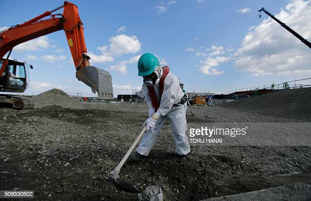 A worker wearing a protective suit and a mask levels ground during a media tour to Tokyo Electric Power Co's tsunamicrippled Fukushima Daiichi...