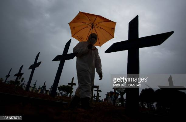 Worker wearing a protective suit and carrying an umbrella walks past the graves of COVID-19 victims at the Nossa Senhora Aparecida cemetery, in...